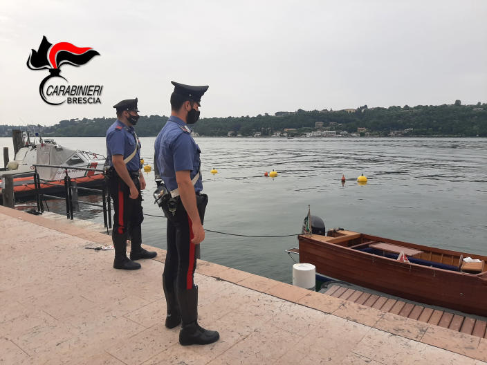 Italian police stand by Lake Garda as they are investigating two German tourists from Munich for a boat collision which killed an Italian man and woman, on Lake Garda, northern Italy, Monday, June 21, 2021. Carabinieri paramilitary police on Monday didn't immediately give details. Italian media said the woman's body was found in the lake by Italian firefighter rescue divers on Sunday evening and that the man's body was found in their small boat earlier in the day. (Carabinieri via AP)
