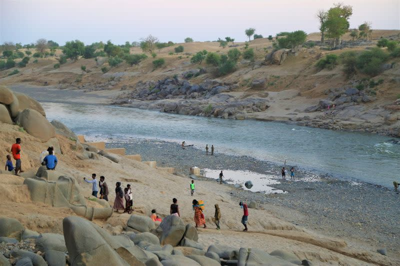 Ethiopians who fled the ongoing fighting in Tigray region, collect water from the Setit river on the Sudan-Ethiopia border in eastern Kassala state