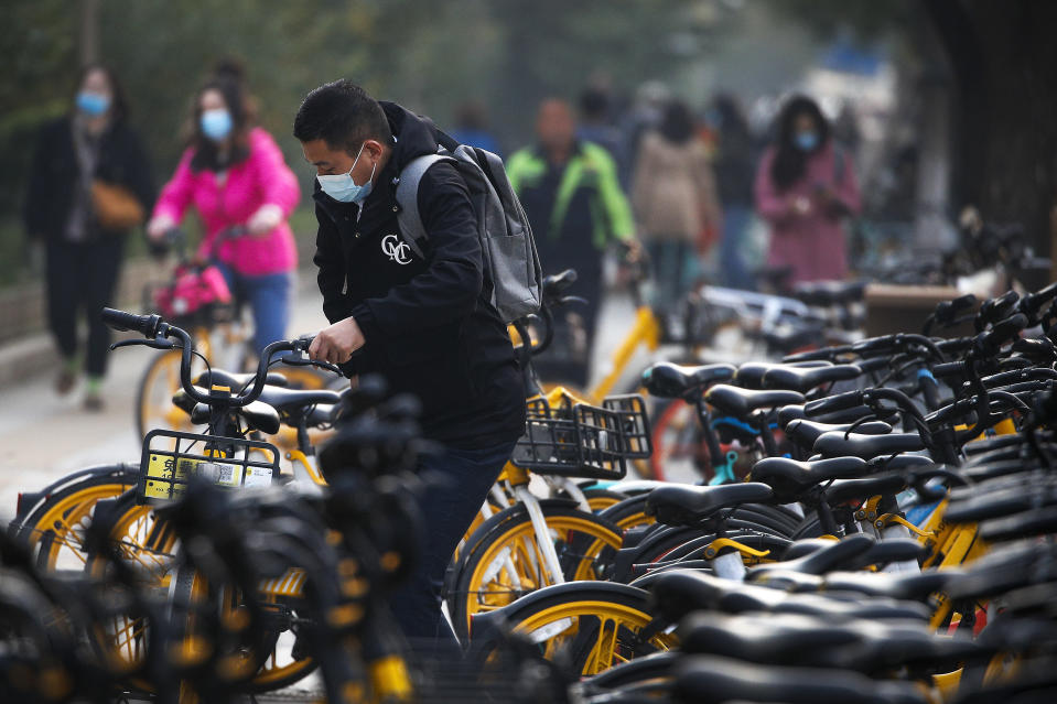 Commuters wearing a face mask to help curb the spread of the coronavirus ride bicycles of bike-sharing companies parked outside a subway station during the morning rush hour in Beijing, Monday, Oct. 26, 2020. Schools and kindergartens have been suspended and communities are on lockdown in Kashgar, a city in China's northwest Xinjiang region, after more than 130 asymptomatic cases of the coronavirus were discovered. (AP Photo/Andy Wong)