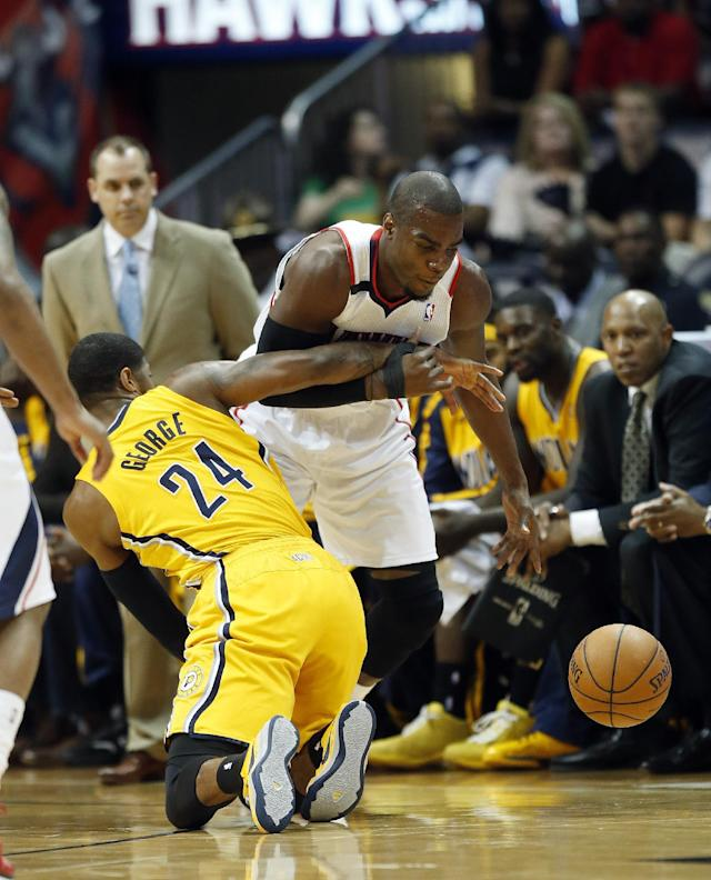 Indiana Pacers forward Paul George (24) tries to steal the ball from Atlanta Hawks forward Paul Millsap (4) in the first half of Game 4 of an NBA basketball first-round playoff series, Saturday, April 26, 2014, in Atlanta. (AP Photo/John Bazemore)