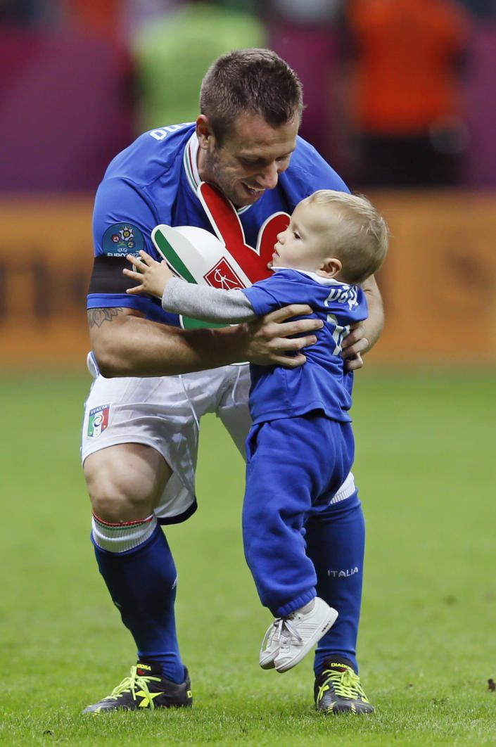 Italy's Antonio Cassano picks up his son Christopher after his team's 2-1 win during the Euro 2012 soccer championship semifinal match between Germany and Italy in Warsaw, Poland, Thursday, June 28, 2012. (AP Photo/Frank Augstein)