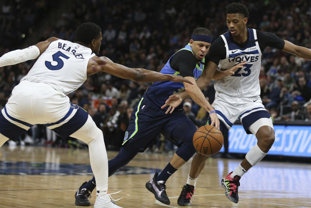 Dallas Mavericks' Seth Curry drives the ball through the defense of Minnesota Timberwolves' Malik Beasley, left, and Jarrett Culver, right, in the second half of an NBA basketball game Sunday, March 1, 2020, in Minneapolis. Dallas won 111-91. (AP Photo/Stacy Bengs)
