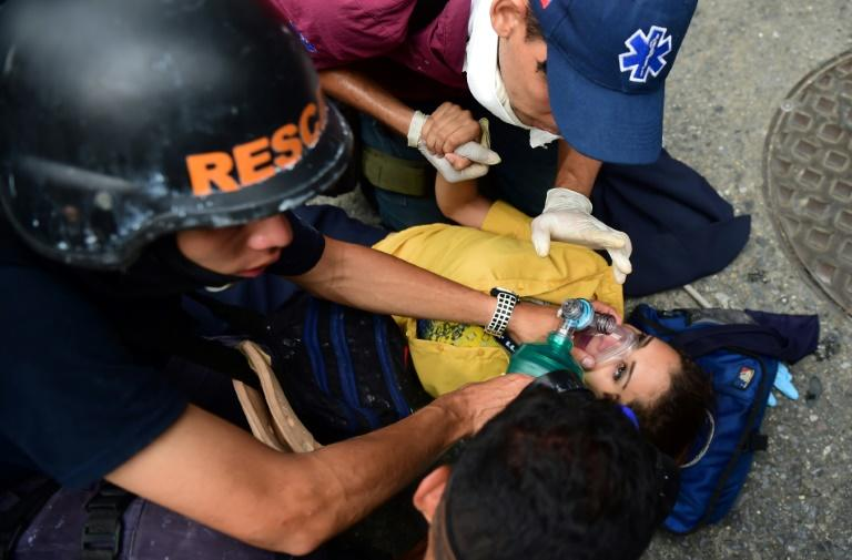 Rescue workers assist a woman after clashes with the riot police during a protest against Venezuelan President Nicolas Maduro, in Caracas on April 20, 2017