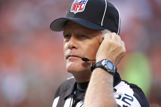 FILE - Down judge Jeff Bergman checks his headset before the New Orleans Saints play the Cleveland Browns in an NFL preseason football game, Thursday, Aug. 10, 2017, in Cleveland. The NFL's longest-serving on-field official was among five who have opted to take a leave of absence for the 2020 season. Bergman, who was entering his 29th year of service, headlined the list released Friday, Aug. 14, 2020 by the NFL. (AP Photo/Ron Schwane)