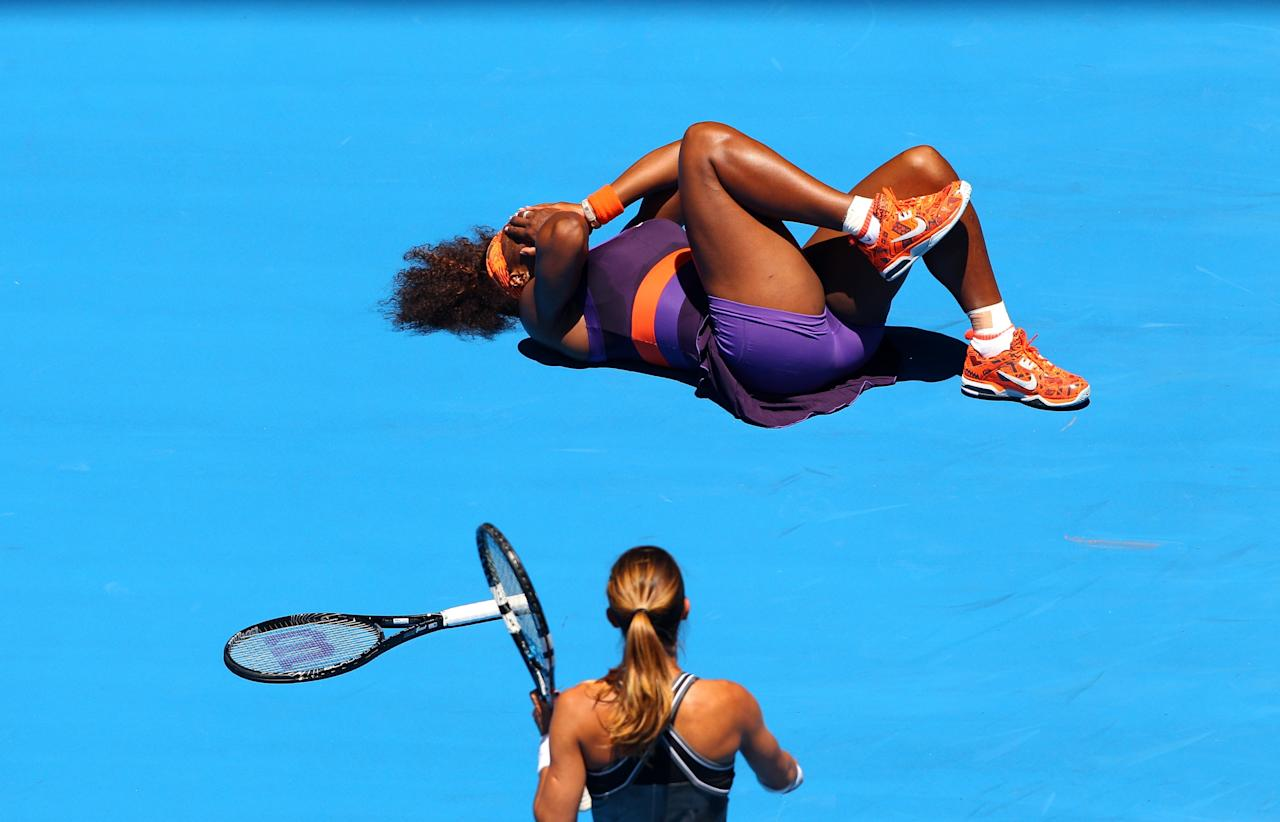 MELBOURNE, AUSTRALIA - JANUARY 15:  Edina Gallovits-Hall of Romania watches on as Serena Williams of the United States lays on the court after falling in her first round match during day two of the 2013 Australian Open at Melbourne Park on January 15, 2013 in Melbourne, Australia.  (Photo by Robert Prezioso/Getty Images)