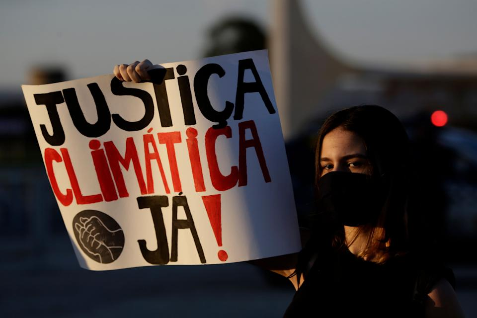 "A woman holds a sign reading ""Climate Justice Now!"" during a protest against Bolsonaro's environmental policies in the Brazilian capital of Brasilia. Bolsonaro has faced domestic and international pressure to alter his approach to the environment. (Photo: AP Photo/Eraldo Peres)"