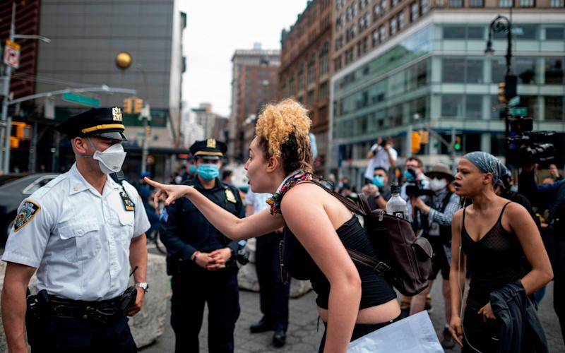 """A protester gestures at an NYPD officer during a """"Black Lives Matter"""" demonstration on May 28, 2020 in New York City, - AFP"""