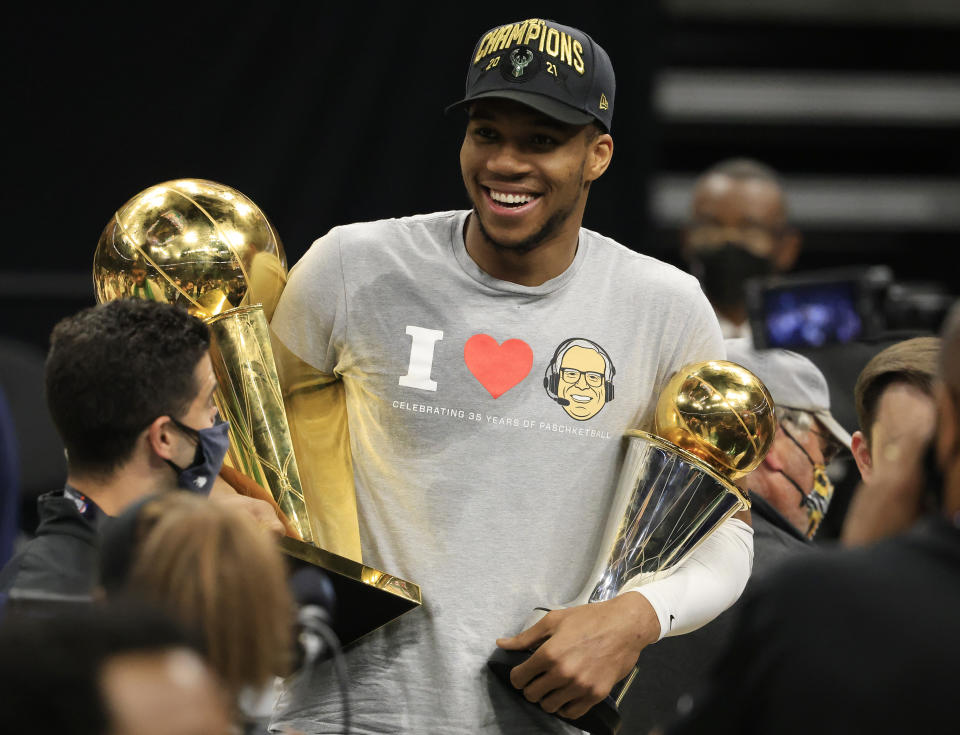 Giannis Antetokounmpo smiles as he holds the Bill Russell NBA Finals MVP Award and the Larry O'Brien Championship Trophy.