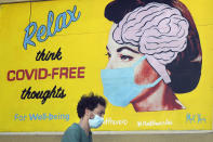 """FILE - In this May 23, 2020, file photo, a man wears a face mask while walking under a sign that reads """"Relax think COVID free thoughts"""" during the coronavirus outbreak in San Francisco. (AP Photo/Jeff Chiu, File)"""
