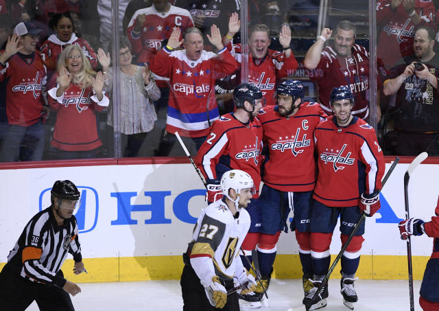 Washington Capitals left wing Alex Ovechkin, top center, of Russia, celebrates his goal with Matt Niskanen, top right, and Evgeny Kuznetsov, of Russia, during the third period of an NHL hockey game as Vegas Golden Knights defenseman Shea Theodore (27) skates by, Wednesday, Oct. 10, 2018, in Washington. The Capitals won 5-2. (AP Photo/Nick Wass)