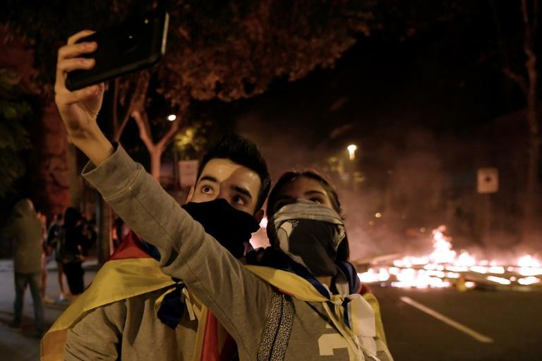Caught on camera: two protesters take a selfie to the backdrop of burning barricades (AFP Photo/LLUIS GENE)