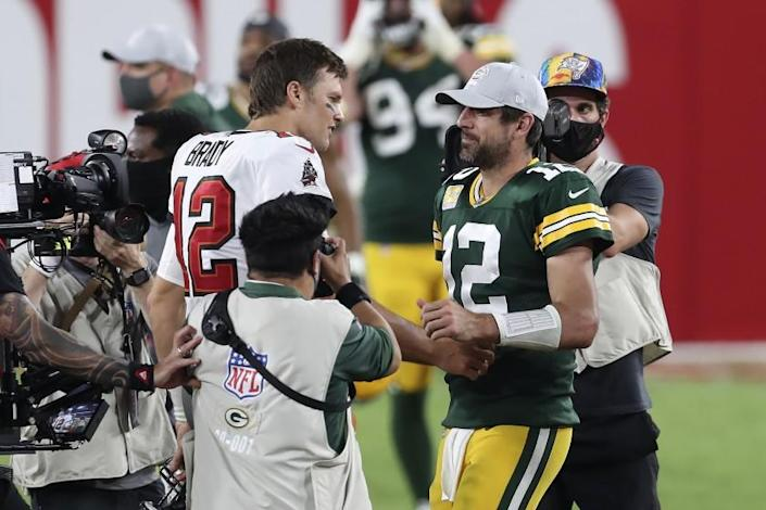 Tampa Bay Buccaneers quarterback Tom Brady, left, shakes hands with Green Bay Packers quarterback Aaron Rodgers.