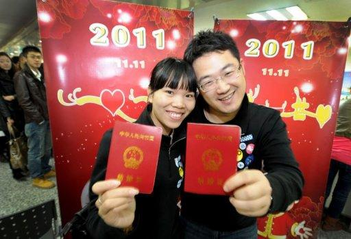 "A Chinese couple show their marriage certificates at a marriage registration office in Hefei, east China's Anhui province, on November 11. Chinese couples flocked to registry offices to marry on in the belief that the ""11.11.11"" date is the most auspicious in a century"