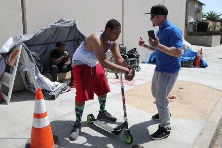 PATH Housing Outreach Case Manager Kris Toriz (R) raps with a homeless man he is helping, in Hollywood, Los Angeles, California, U.S. April 13, 2018. Picture taken April 13, 2018. REUTERS/Lucy Nicholson
