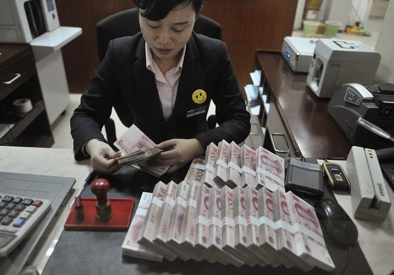 A clerk counts 100 Chinese yuan banknotes at a branch of China Merchants Bank in Hefei