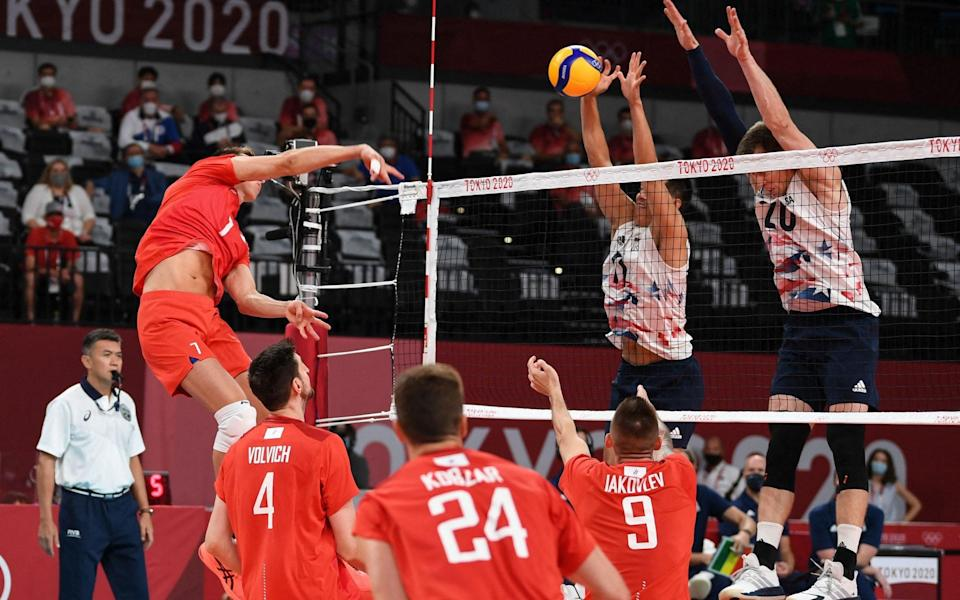Russia's Dmitry Volkov (L) spikes the ball in the men's preliminary round pool B volleyball match between USA and Russia - AFP