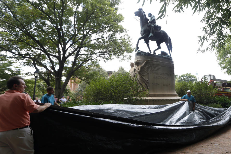FILE - In this Aug. 23, 2017, file photo, city workers prepare to drape a tarp over the statue of Confederate Gen. Stonewall Jackson in Court Square Park, formerly Justice Park, in Charlottesville, Va. Charlottesville officials have voted unanimously to remove two statues of Confederate generals Robert E. Lee and Stonewall Jackson from two downtown parks including one that was the focus of a violent white nationalist rally in 2017. News outlets report that the vote came late Monday, June 7, 2021, after more than 50 people spoke during a virtual meeting, most in favor of removal. (AP Photo/Steve Helber, File)