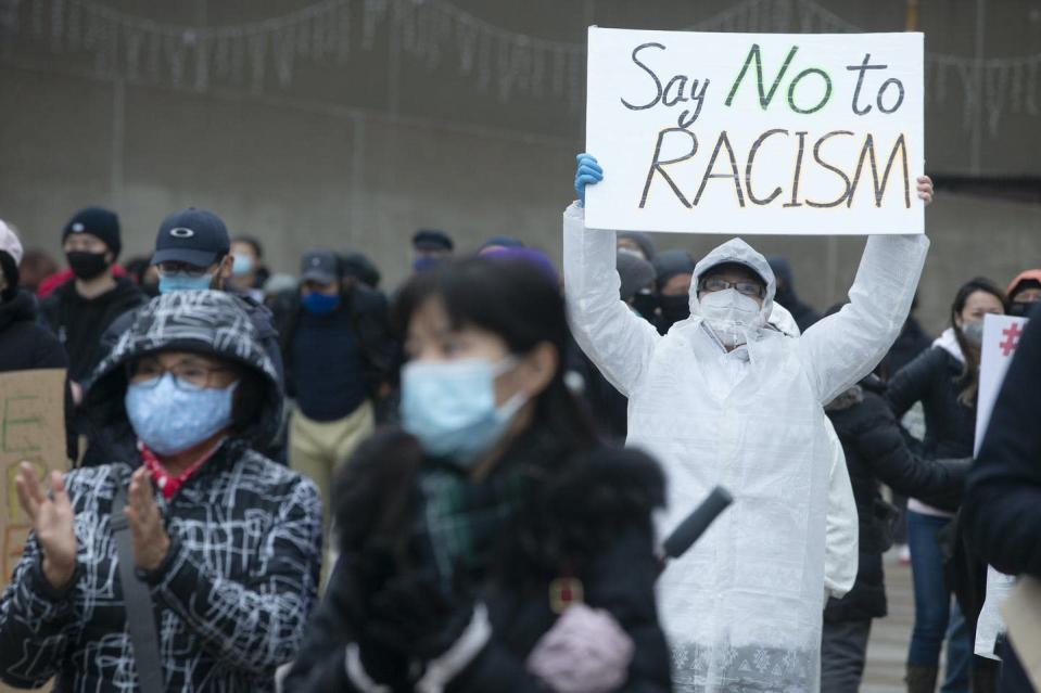 """<span class=""""caption"""">People wearing masks attend a rally opposing discrimination against Asian communities in Toronto in March 2021.</span> <span class=""""attribution""""><span class=""""source""""> THE CANADIAN PRESS/Chris Young </span></span>"""