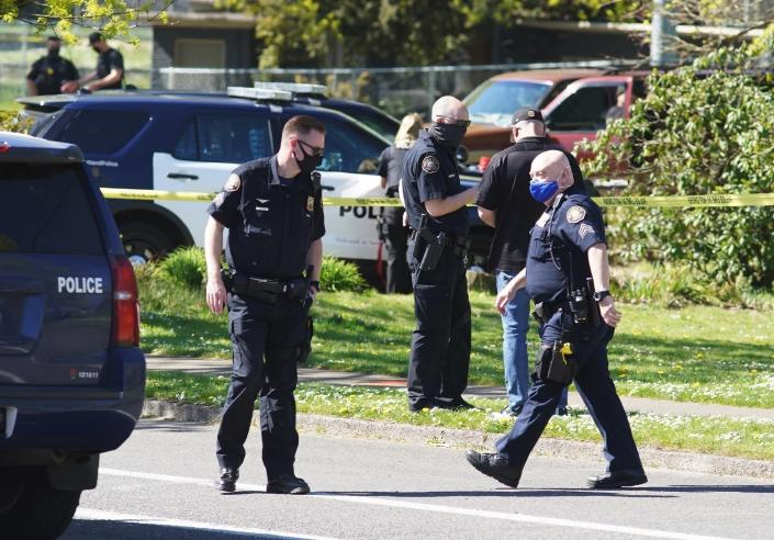 FILE - In this Friday, April 16, 2021, file photo, law enforcement personnel work at the scene following a police-involved shooting of a man at Lents Park, in Portland, Ore. Police fatally shot a man in the city park Friday, April 30, 2021 after responding to reports of a person with a gun. Unlike shootings involving police around the country there was no body camera footage of this encounter. Portland, which has become the epicenter of racial justice protests, is one of the few major U.S. cities where police do not have body cameras. (Beth Nakamura/The Oregonian via AP, File)