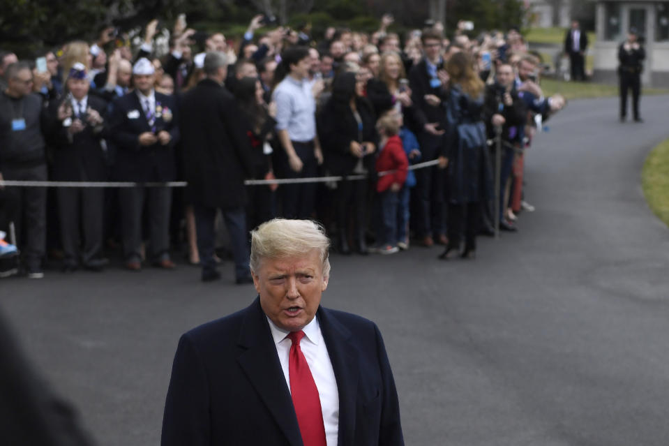 President Donald Trump briefly talks with reporters before boarding Marine One on the South Lawn of the White House in Washington, Monday, Jan. 13, 2020. He, and first lady Melania Trump who is greeting people in the background, are heading to New Orleans to attend the College Football Playoff National Championship between Louisiana State University and Clemson. (AP Photo/Susan Walsh)