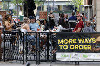 "FILE—This file photo from June 28, 2020 shows people gathering at tables outside Bar Louie in Pittsburgh. Pennsylvania is imposing broad new statewide restrictions on bars and restaurants and larger indoor gatherings, with Gov. Tom Wolf citing an ""alarming escalation"" in new coronavirus infections on Wednesday, July, 15, 2020. (AP Photo/Gene J. Puskar, File)"