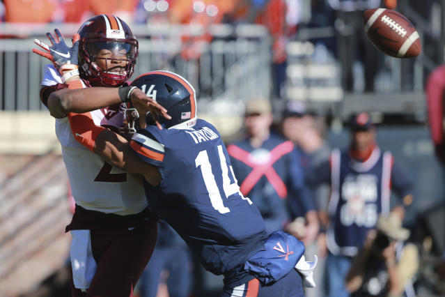 Virginia Tech quarterback Hendon Hooker (2) is hit by Virginia linebacker Noah Taylor (14) as he throws the ball during the first half of an NCAA college football game between Virginia Tech and Virginia in Charlottesville, Va., Friday, Nov. 29, 2019. (AP Photo/Steve Helber)