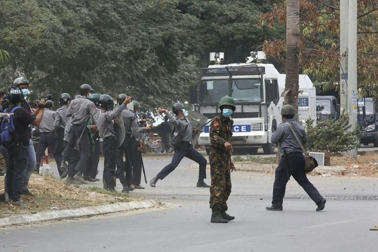 Police throw projectiles towards protesters during the Mandalay disturbance