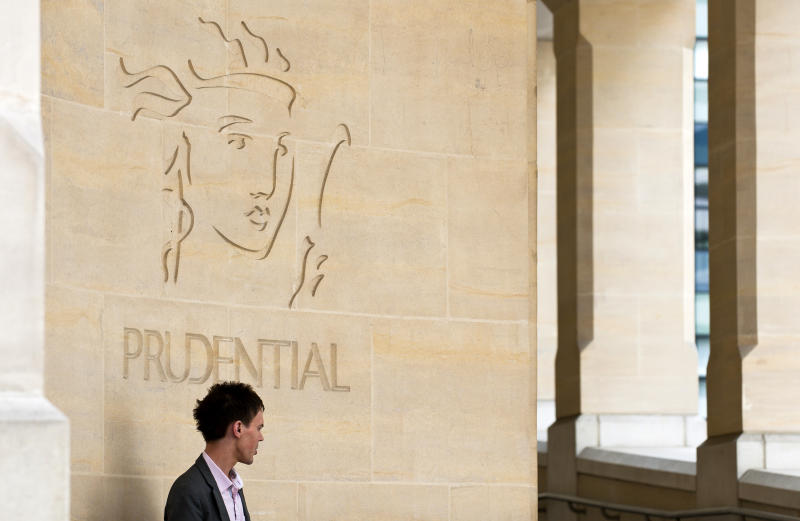 A pedestrian pauses by the Prudential Plc company logo. Photo: Frantzesco Kangaris/Bloomberg