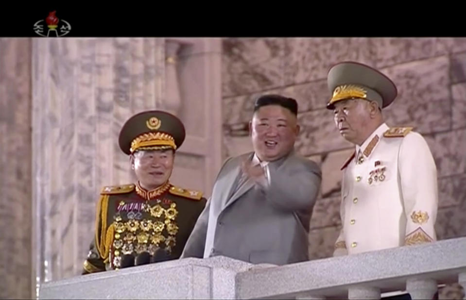 In this image made from video broadcasted by North Korea's KRT, North Korean leader Kim Jong Un, center, watches military parade during a ceremony to celebrate the 75th anniversary of the country's ruling party in Pyongyang Saturday, Oct. 10, 2020.(KRT via AP)