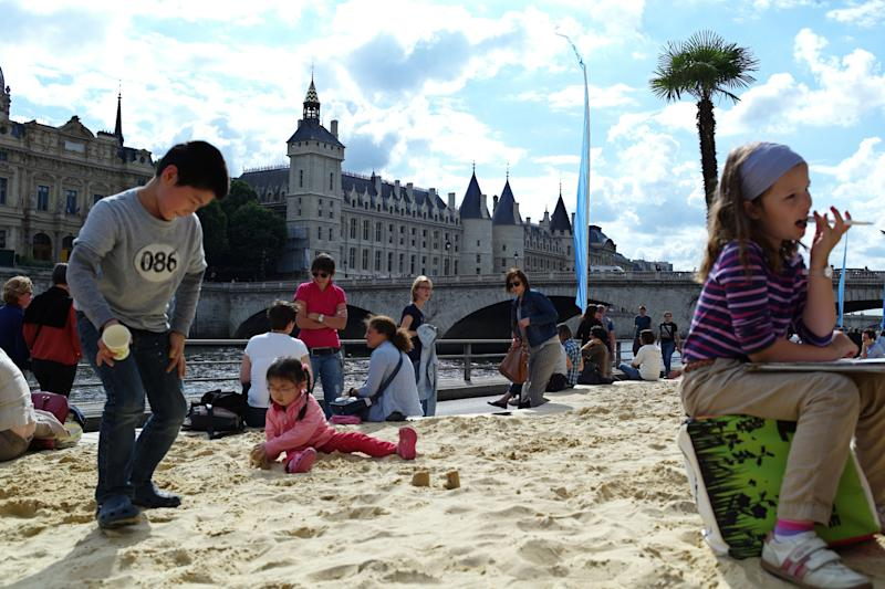 In this July 20, 2012 file photo, children play in sand during the Paris Plages event in Paris, featuring palm trees, sand beaches, hammocks, lounge chairs, volley ball courts and a pool line the 3.5-kilometer (2.2-mile) riverside attraction. Paris Plages or Paris Beaches, is a free summer event that transforms several spots along the Seine river into complete beaches. (AP Photo/Thibault Camus, File)