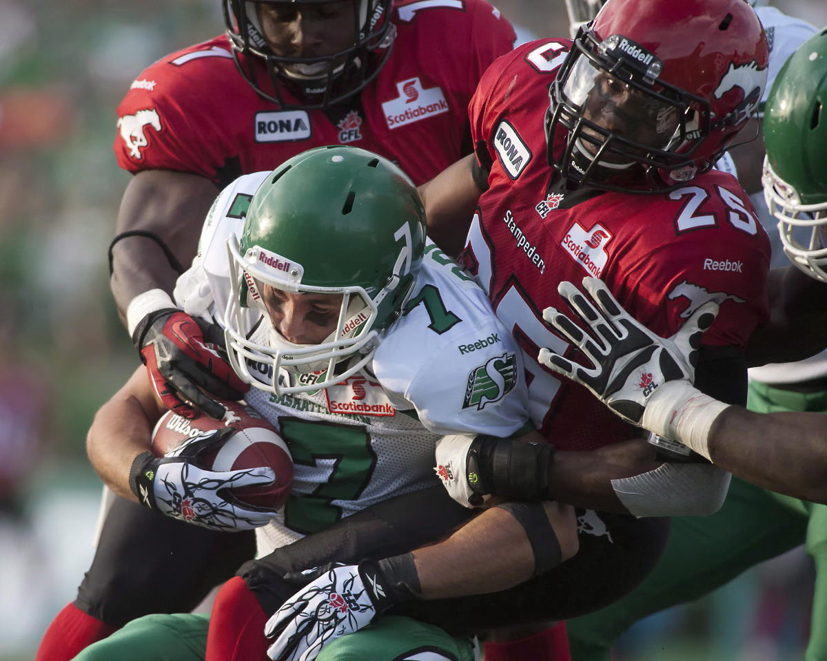 Saskatchewan Roughriders slotback Weston Dressler is tackled in the first half of CFL pre-season football action against the Calgary Stampeders in Regina, Sask., Friday, June 22, 2012. THE CANADIAN PRESS/Liam Richards