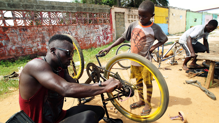 Odixco F Gongoar, owner of God Bless Bicycle Repair Center, repairs a bicycle as a trainee looks on in Paynesville, Liberia - Monday 24 May 2021