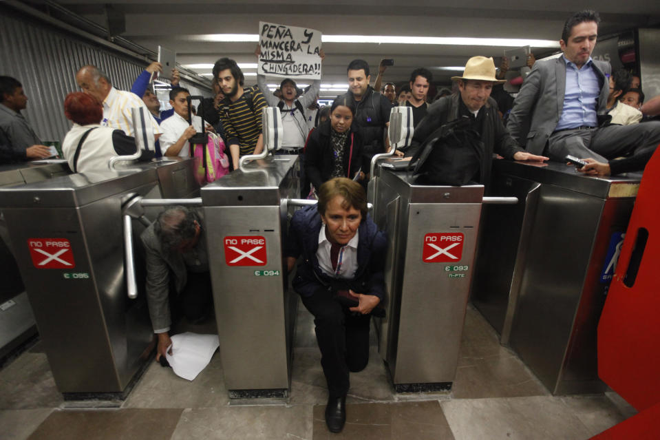 People duck under and jump over the turnstiles without paying to protest against a fare hike, at Pino Suarez subway station in Mexico City December 12, 2013. According to local media, Mexico City authorities raised the subway fare from 3 Pesos to 5 Pesos, an approximate increase of $0.15, starting December 13. The sign reads