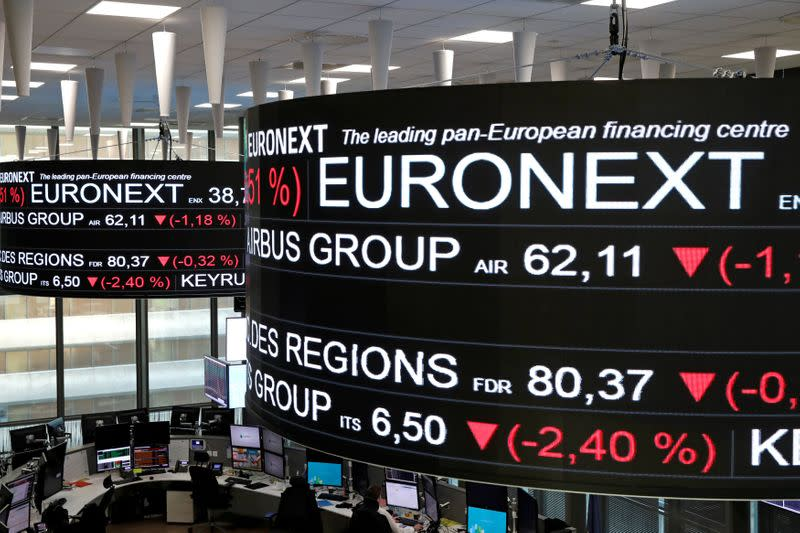 FILE PHOTO: Company stock price information are displayed on screens as they hang above the Paris stock exchange, operated by Euronext NV, in La Defense business district in Paris