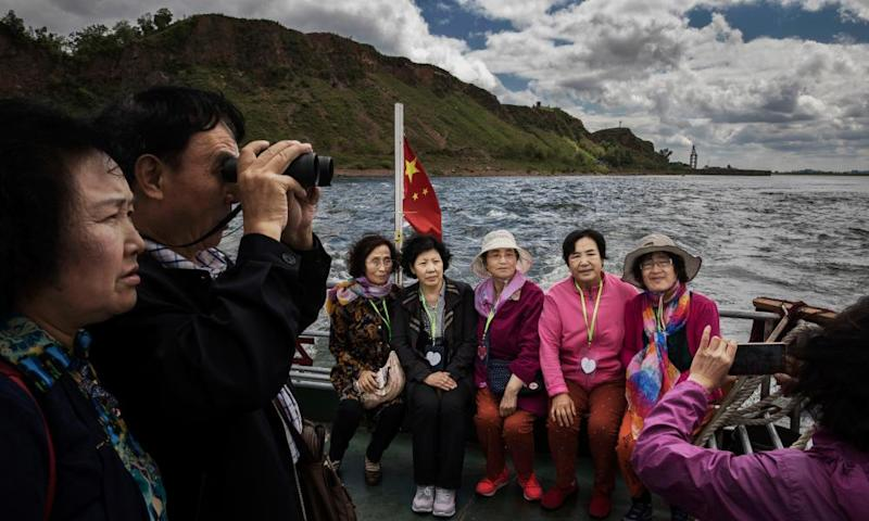 Chinese tourists ride in a boat on the Yalu river with North Korean territory on both sides north of the border city of Dandong.