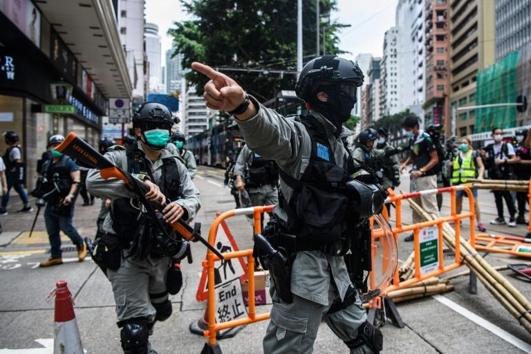 Riot police clear debris left by protesters attending a pro-democracy rally on May 24, 2020 against a proposed new security law China plans to impose on the territory