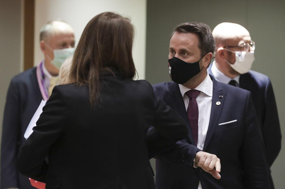 Luxembourg's Prime Minister Xavier Bettel, center, greets Belgium's Prime Minister Sophie Wilmes with an elbow bump during a round table meeting at an EU summit in Brussels, Friday, July 17, 2020. Leaders from 27 European Union nations meet face-to-face on Friday for the first time since February, despite the dangers of the coronavirus pandemic, to assess an overall budget and recovery package spread over seven years estimated at some 1.75 trillion to 1.85 trillion euros. (Stephanie Lecocq, Pool Photo via AP)