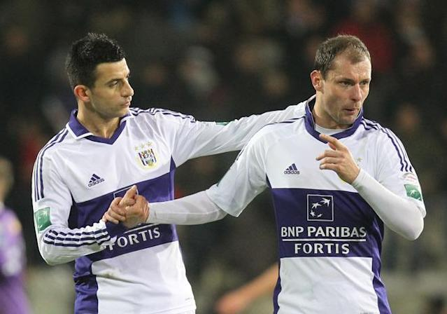 Anderlecht's Behrang Safari and Anderlecht's Milan Jovanovic hold hands after the Jupiler Pro League match between Beerschot AC and RSC Anderlecht, in Antwerp, on January 28, 2012, on the 23rd day of the Belgian soccer championship. AFP PHOTO /VIRGINIE LEFOUR