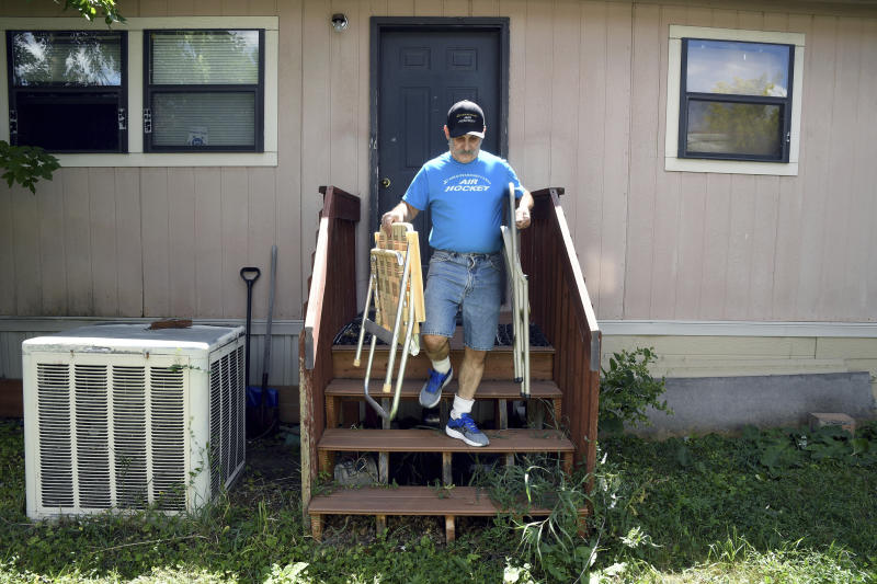 ADVANCE ON THURSDAY, SEPT. 12 FOR USE ANY TIME AFTER 3:01 A.M. SUNDAY SEPT 15  Mark Robbins removes lawn chairs from his home at the Orchard Grove Mobile Home Park in Boulder, Colo., on Monday, Aug. 26, 2019. Robbins, who moved to the park in 1982 and is a member of the neighborhood association, says residents have been subjected to illegal evictions and onerous rules since the park was sold in 2015. (AP Photo/Thomas Peipert)