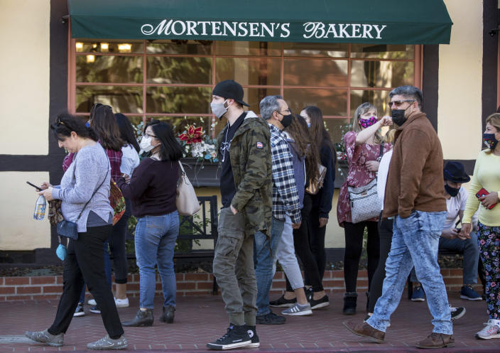 Groups of people, some wearing masks, take over the sidewalks downtown in Solvang, California, on Nov. 28, 2020. It was almost two weeks ago that the popular California tourist town of Solvang made headlines when it said it wouldn't enforce Gov. Gavin Newsom's tough new stay-at-home orders. But that was a week before a new City Council took over and told everyone to obey the rules to save lives. (George Rose/Santa Ynez Valley Star via AP)