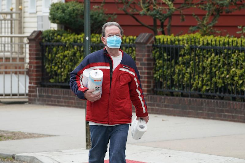A man wearing a mask carries toilet paper and paper towels in the Bushwick section of Brooklyn April 5, 2020 in New York. - The coronavirus death toll in New York state spiked to 4,159, the governor said, up from 3,565 a day prior. The toll increase of 594 showed a slight decrease in the day-to-day number of lives lost compared to the previous day. Governor Andrew Cuomo told journalists it was too soon to tell whether the decrease from the previous record of 630 deaths in one day was statisically significant. (Photo by Bryan R. Smith / AFP) (Photo by BRYAN R. SMITH/AFP via Getty Images)