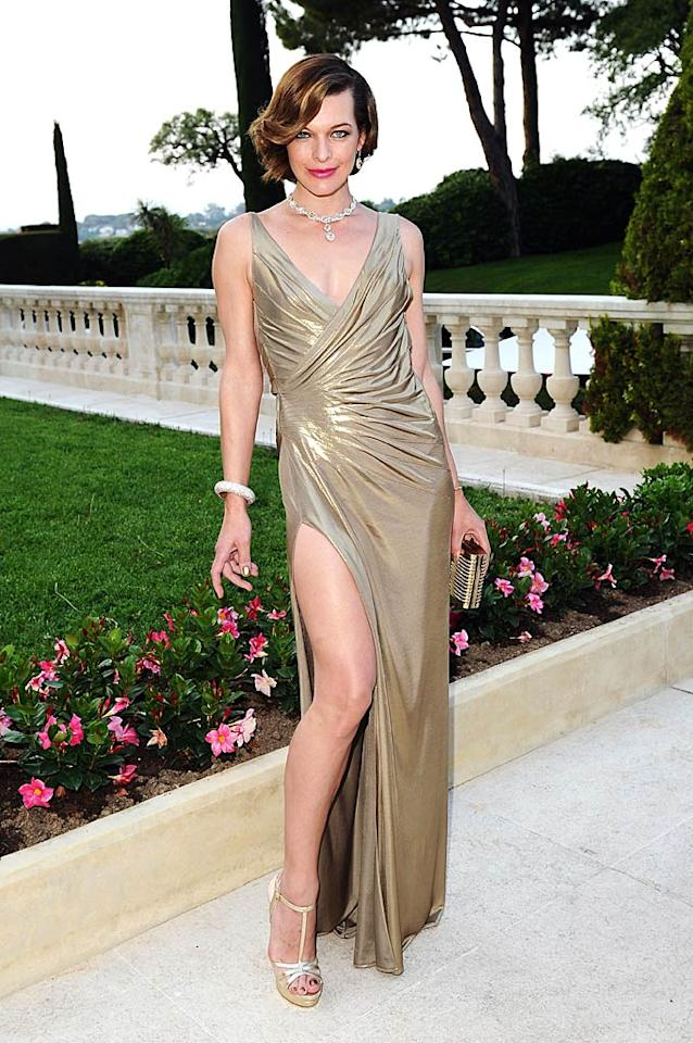 "Despite jamming her foot into an uncomfortable-looking pair of T-strap platform sandals, Milla Jovovich looked flawless in the south of France (at the amfAR fete) thanks to her revealing, gold Atelier Versace gown and exquisite baubles. Ian Gavan/<a href=""http://www.gettyimages.com/"" target=""new"">GettyImages.com</a> - May 19, 2011"