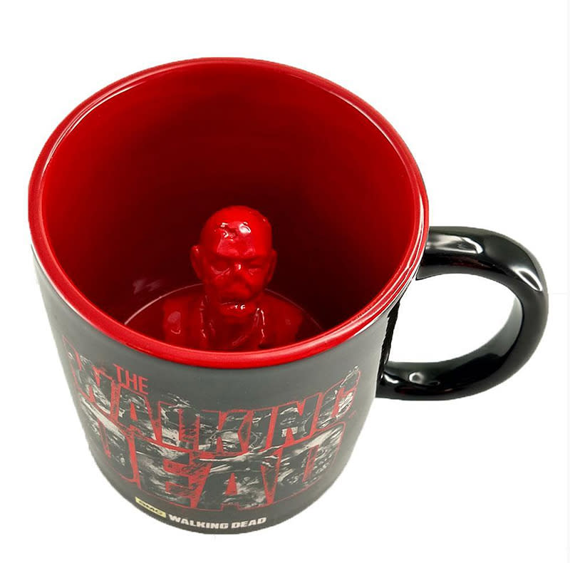 "<p>On the outside, it's a <a rel=""nofollow"" href=""https://www.shopthewalkingdead.com/collections/drinkware/products/the-walking-dead-molded-zombie-mug?variant=29637983314"">perfectly fine mug</a>, featuring <i>The Walking Dead</i> logo in red, filled with black and white photos of walkers. But as you tip back the cup and drain it of its hot beverage goodness, there's a surprise waiting for you: a zombie in your coffee! The little red ceramic dude is permanently anchored to the bottom of your cup, so there's your ""waking the dead"" coffee!<br />(Photo: shopthewalkingdead.com) </p>"