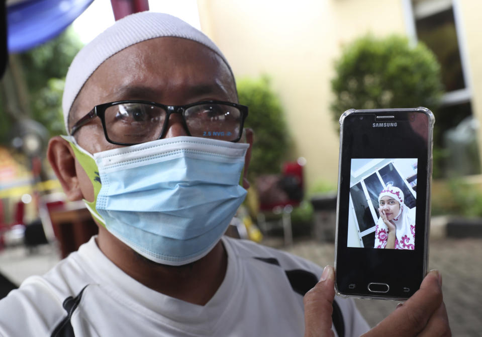 Habib Sy Rafik al Idrus shows a picture of his wife Panca Widia Nursanti, one of passengers of a Sriwijaya Air jet that crashed into the sea, at a hospital in Jakarta, Indonesia, Tuesday, Jan. 12, 2021. Indonesian navy divers were searching through plane debris and seabed mud Tuesday looking for the black boxes of the jet that nosedived into the Java Sea over the weekend with 62 people aboard. (AP Photo/Achmad Ibrahim)
