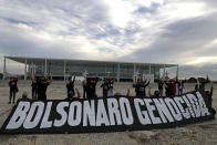 """Demonstrators hold crosses to represent people who have died of COVID-19 behind the Portuguese phrase """"Bolsonaro genocide"""" as they protest the president's handling of the COVID-19 pandemic outside Planalto presidential palace in Brasilia, Brazil, Friday, March 19, 2021. (AP Photo/Eraldo Peres)"""