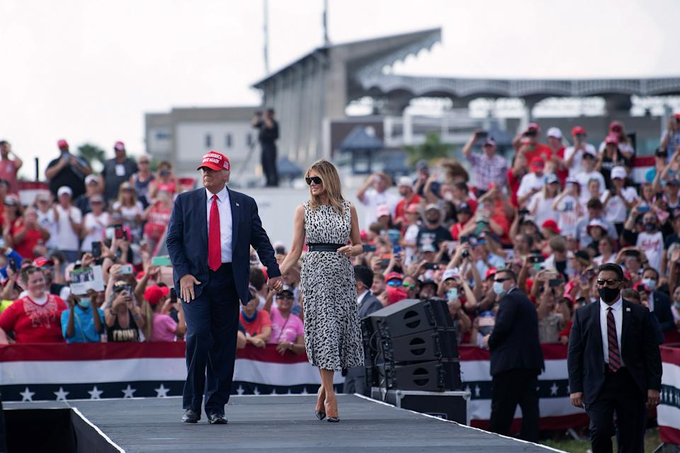 TOPSHOT - US President Donald Trump and US first lady Melania Trump leave after speaking during a Make America Great Again rally in Raymond James Stadium's parking lot October 29, 2020, in Tampa, Florida. (Photo by Brendan Smialowski / AFP) (Photo by BRENDAN SMIALOWSKI/AFP via Getty Images)