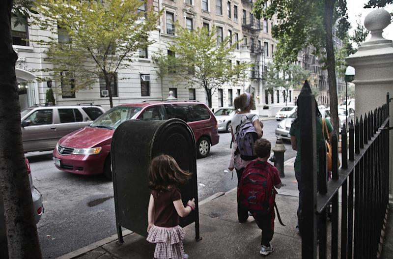 Youngsters walk with their escorts across the street from a shelter on 95th Street on Wednesday, Oct. 3, 2012 in New York. Neighborhood residents are in turmoil, saying they were blindsided by the suddenness of the shelter's opening, sharing the same block as the school. (AP Photo/Bebeto Matthews)