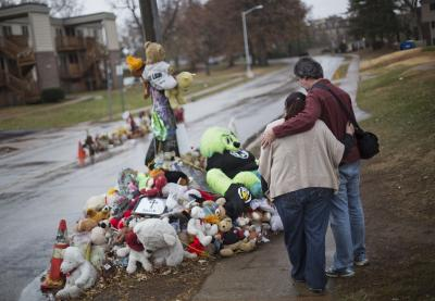 Ferguson residents Lisa Tebbe and John Powell embrace at the site where Michael Brown died. (AP Photo/David Goldman)