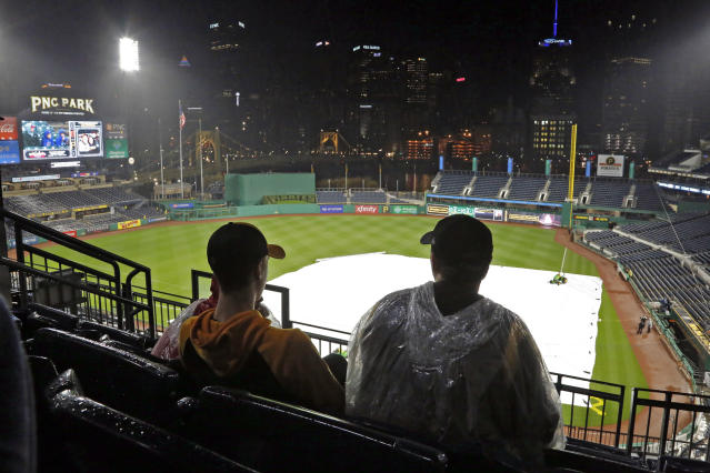 Fns watch the Cleveland Indians against the Chicago Cubs game from Cleveland,on the scoreboard at PNC Park in Pittsburgh, during a rain delay before a scheduled baseball game between the Pittsburgh Pirates and the Detroit Tigers in Pittsburgh, Tuesday, April, 24, 2018. The game was postponed due to a steady rain, and was re-scheduled as part of a doubleheader Wednesday. (AP Photo/Gene J. Puskar)