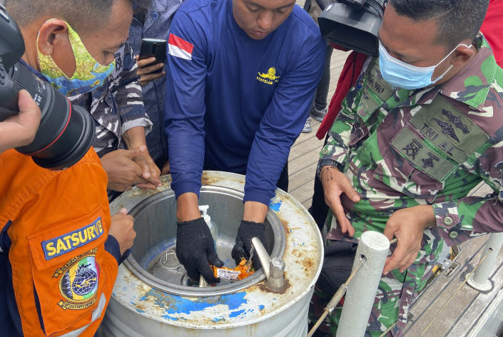Indonesian navy personnel inspect a part the flight data recorder of Sriwijaya Air flight SJ-182 retrieved from the Java Sea where the passenger jet crashed in waters off the Tanjung Priok Port, Tuesday, Jan. 12, 2021. Indonesian navy divers searching the ocean floor on Tuesday recovered the flight data recorder from a Sriwijaya Air jet that crashed into the Java Sea with 62 people on board, Saturday, Jan. 9, 2021. (AP Photo/Fadlan Syam)
